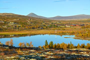 Overview of the area around the hotel with mirror lake, mountains and fall colors. Spidsbergseter Resort Rondane.