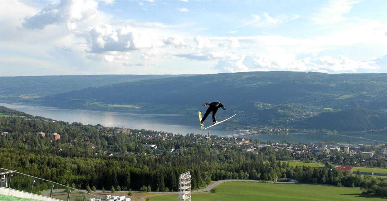 A ski jumper in action - with a view of Lillehammer city